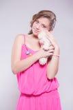 Mädchen in einem rosa Kleid, das einen Teddybären hält Stockbild