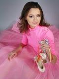 Mädchen in einem rosafarbenen Kleid zeigt Fußbekleidung lizenzfreies stockfoto