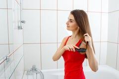 Mädchen in einem roten Hemd steht im Badezimmer und kämmt ihr Haar Lizenzfreie Stockbilder