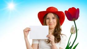Mädchen in einem roten Hut mit Tulpen Lizenzfreies Stockfoto