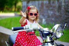 Mädchen in einem roten Kleid auf einem Motorrad Lizenzfreies Stockbild