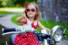 Mädchen in einem roten Kleid auf einem Motorrad Lizenzfreies Stockfoto
