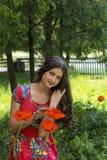 Mädchen in einem roten Kleid auf Hintergrund der Mohnblume Stockbilder
