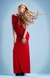 Mädchen in einem roten Kleid mit dem Fliegenhaar Stockbilder
