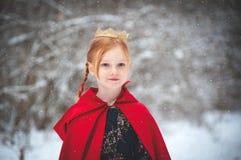 Mädchen in einem roten Mantel mit einer Goldkrone lizenzfreies stockbild