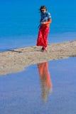Mädchen in einem roten Rock gehend auf den Sand entlang dem Strand Stockfotografie