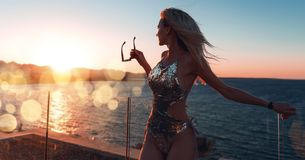 Mädchen in einem schönen Badeanzug bei Sonnenuntergang durch das Meer, das Sonnenbrille hält lizenzfreie stockfotografie