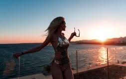 Mädchen in einem schönen Badeanzug einen schönen Sonnenuntergang bewundernd lizenzfreies stockbild
