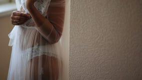 Mädchen in einem schönen weißen peignoir am Fenster stock footage