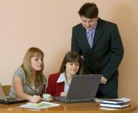 Mädchen an einem Schreibtisch und an ihrem Leiter Stockfotos