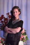 Mädchen in einem schwarzen Kleid nahe bei einem Vase mit Blumen Stockbild
