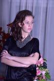 Mädchen in einem schwarzen Kleid nahe bei einem Vase mit Blumen Stockfotos