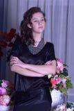 Mädchen in einem schwarzen Kleid nahe bei einem Vase mit Blumen Stockbilder
