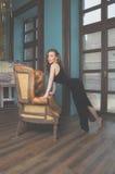 Mädchen in einem schwarzen Kleid steht nahe der Couch Stockfoto
