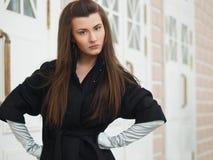 Mädchen in einem schwarzen Mantel lizenzfreie stockfotos