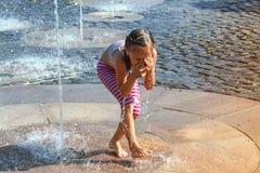Mädchen an einem sonnigen warmen Tag, der draußen in einem Wasserbrunnen spielt Mädchen glücklich im seichten Trinkwasser an des  stockfotos