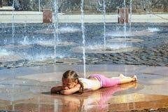 Mädchen an einem sonnigen warmen Tag, der draußen in einem Wasserbrunnen spielt Mädchen glücklich im seichten Trinkwasser an des  lizenzfreie stockfotos