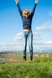 Mädchen in einem Sprung über einer Klippe mit Ansichten der Stadt Lizenzfreie Stockfotos