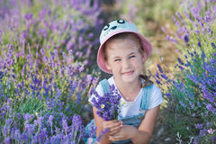 Mädchen in einem Strohhut auf einem Gebiet des Lavendels mit einem Korb des Lavendels Ein Mädchen auf einem Lavendelgebiet Mädche Lizenzfreie Stockfotos