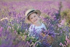 Mädchen in einem Strohhut auf einem Gebiet des Lavendels mit einem Korb des Lavendels Ein Mädchen auf einem Lavendelgebiet Mädche Lizenzfreie Stockbilder