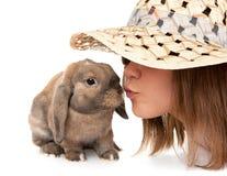 Mädchen in einem Strohhut küßt zwergartiges Kaninchen. Lizenzfreie Stockbilder