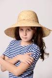 Mädchen in einem Strohhut und in einem gestreiften Hemd Stockbilder