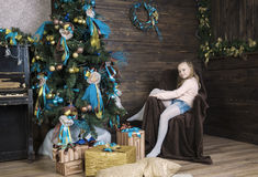 Mädchen in einem Stuhl auf dem Hintergrund des Weihnachtsbaums Stockbild