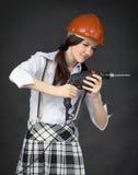 Mädchen in einem Sturzhelm erlernt, ein Bohrgerät zu benutzen Stockfotografie