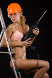 Mädchen in einem Sturzhelm mit einem Bohrgerät Stockfotografie