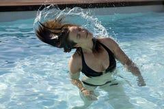 Mädchen in einem Swimmingpool, der nasses Haar wirft Lizenzfreie Stockfotos
