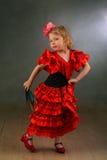 Mädchen in einem Tanzen des schicken Kleids mit einem Fan Lizenzfreie Stockbilder
