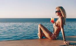 Mädchen in einem teuren Badeanzug mit einem Cocktail in ihren Händen verbringt ihre Ferien nahe dem Pool am Erholungsort lizenzfreies stockbild