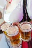 Mädchen in einem Trachtenkleid mit große Brüste und tiefer Ausschnitt hält volle Becher Bier Lizenzfreie Stockfotografie