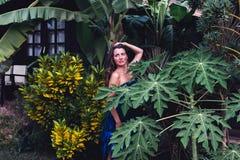 Mädchen in einem tropischen Erholungsort in einem blauen Kleid Stockbild