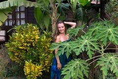 Mädchen in einem tropischen Erholungsort in einem blauen Kleid Stockfotografie