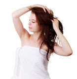 Mädchen in einem Tuch, nachdem eine Dusche, ihr Haar mit seinen Händen geraderichtet Lizenzfreie Stockfotos