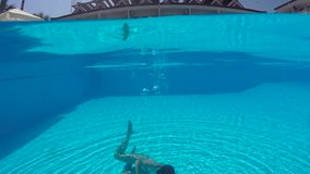Mädchen in einem weißen Badeanzug schwimmend unter Wasser im Pool stock video footage
