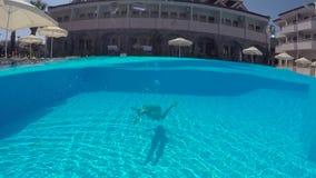 Mädchen in einem weißen Badeanzug schwimmend unter Wasser im Pool stock footage