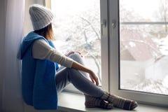 Mädchen in einem weißen Hut und in einer blauen Weste sitzt Stockfotos