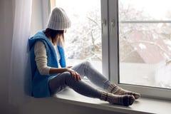 Mädchen in einem weißen Hut und in einer blauen Weste sitzt Stockbilder