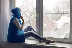 Mädchen in einem weißen Hut und in einer blauen Weste sitzt Stockfoto