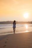 Mädchen in einem weißen Kleid bei Sonnenuntergang Lizenzfreie Stockfotos