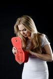 Mädchen in einem weißen Kleid und in einer roten Handtasche Stockfotografie