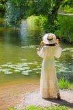 Mädchen in einem weißen Kleid und in einem Hut auf dem Ufer von einem Teich mit wasser- Lizenzfreie Stockfotos
