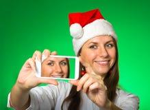 Mädchen in einem Weihnachtshut auf einem grünen Hintergrund Lizenzfreie Stockbilder