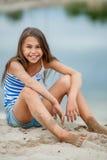 Mädchen in einer gestreiften Weste auf dem Sand Stockfotografie