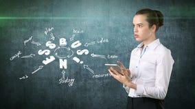 Mädchen in einer Klagenholdingauflage nahe der Wand mit einer Geschäftsideenskizze gezeichnet auf sie Konzept einer erfolgreichen Lizenzfreies Stockfoto