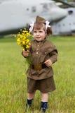 Mädchen in einer Militäruniform mit wilden Blumen in a Stockfotos