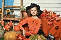 Mädchen in einer orange Strickjacke und in einem Hut in Halloween-Hexe Stockfotos