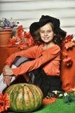 Mädchen in einer orange Strickjacke und in einem Hut in Halloween-Hexe Lizenzfreie Stockfotografie